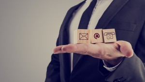 Retro style image of a businessman holding three wooden cubes with contact symbols - envelope, at sign and telephone - conceptual of communication and business support.